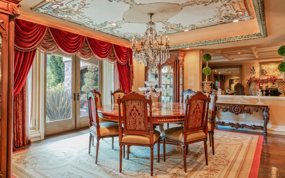 This formal dining room has large glass doors that let in an abundance of natural lighting to brighten the dark wooden dining table topped with a crystal chandelier. Images courtesy of Toptenrealestatedeals.com.