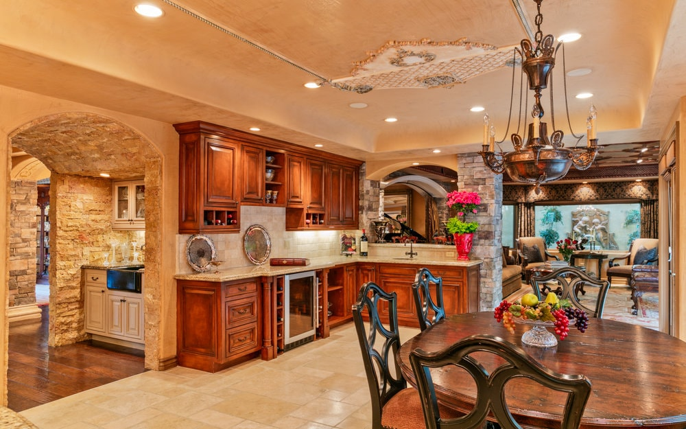 This is the informal dining area just beside the kitchen. It has a dark wooden dining table topped with a small chandelier hanging from the beige ceiling that has intricate details. Images courtesy of Toptenrealestatedeals.com.