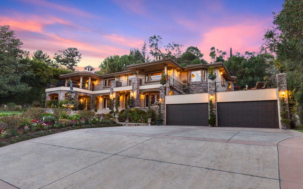 This is the front view of the beautiful house with warm outdoor lighting on its exteriors. It has a large concrete driveway and a beautiful antique stone fountain that serves as a nice foreground. Images courtesy of Toptenrealestatedeals.com.