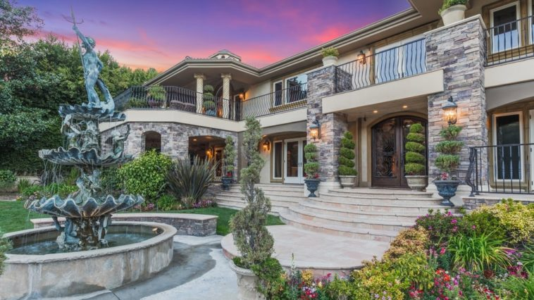 This is a close look at the main entry of the house adorned with a large centuries-old stone fountain. This leads to concrete steps that are adorned with various colorful flowering shrubs on the sides. Images courtesy of Toptenrealestatedeals.com.