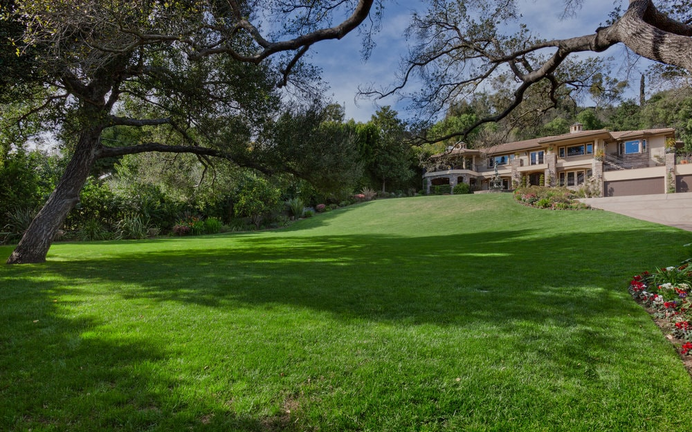 There is a large lawn of grass in front of the house surrounded by lush shrubs and tall trees giving the house a sense of isolation. Images courtesy of Toptenrealestatedeals.com.