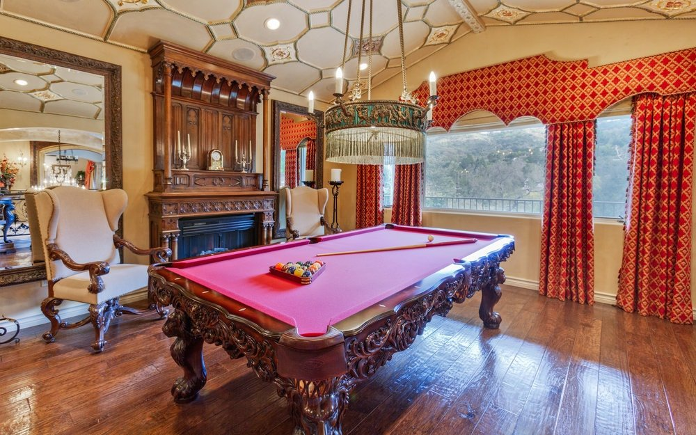 The highlight of this game room is the luxurious pool table with a gorgeous dark wooden frame with intricate carvings to match the intricate ceiling and dark hardwood flooring. Images courtesy of Toptenrealestatedeals.com.