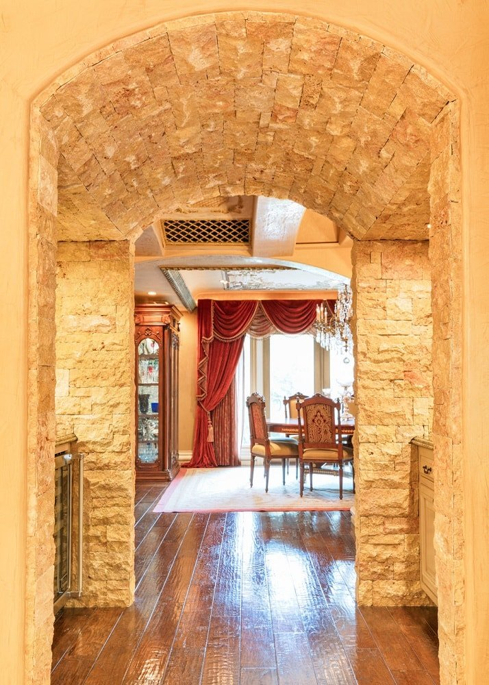 This is the arched hallway that leads to the dining room. It has charming textured beige walls that is complemented by the warm yellow glow of the lamps on each side of the arch. Images courtesy of Toptenrealestatedeals.com.