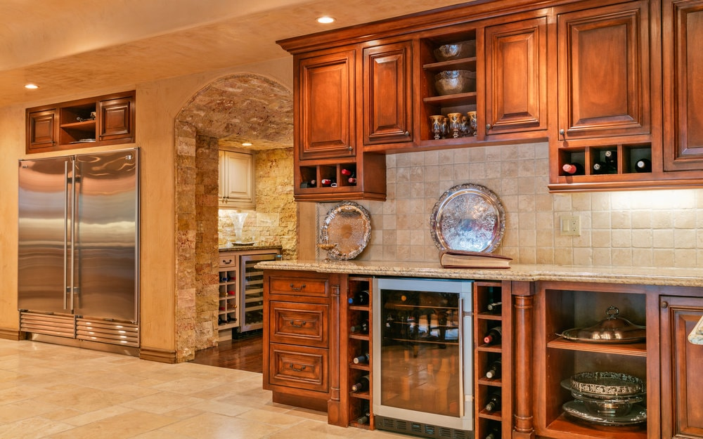 This close look at the kitchen features the large stainless steel fridge embedded into the beige wall. There is also a wooden structure with cabinets and drawers housing a wine fridge. Images courtesy of Toptenrealestatedeals.com.