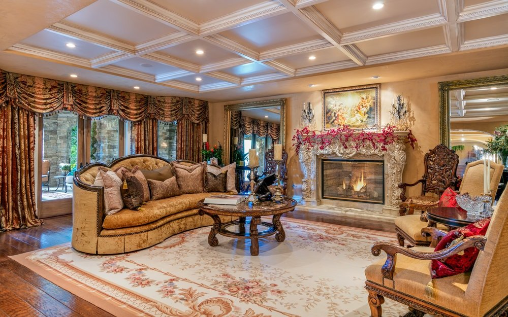 This is the formal living room with a white coffered ceiling, beige walls and a fireplace that is adorned by its mantle that is filled with intricate carvings. Images courtesy of Toptenrealestatedeals.com.