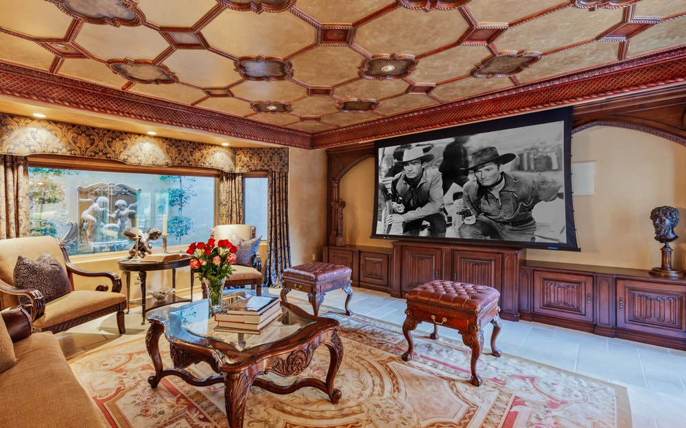 The media room has intricate details on its ceiling and area rug. These are then complemented by the lovely moldings and cabinetry that match the glass-top coffee table. Images courtesy of Toptenrealestatedeals.com.
