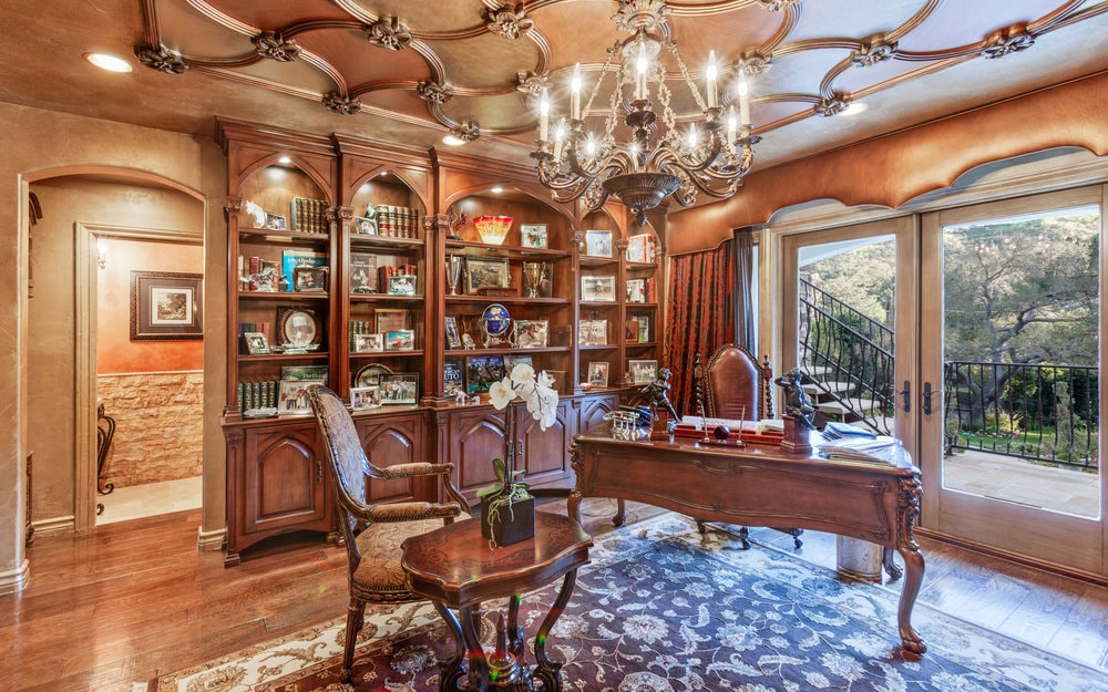 This lush and luxurious home office has a beautiful intricate ceiling that matches the wooden built-in shelves of the wall. This ceiling hangs a majestic chandelier over the wooden desk by the large window. Images courtesy of Toptenrealestatedeals.com.