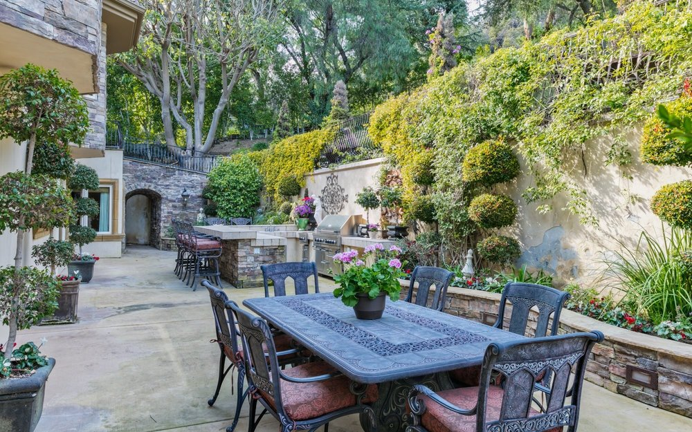 On one side side of the house, there is an outdoor dining area with a wrought-iron dining set. On the far side is the outdoor kitchen. Images courtesy of Toptenrealestatedeals.com.