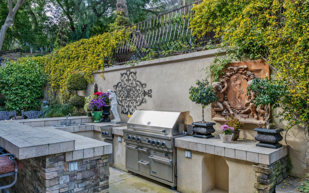 A closer look at this outdoor kitchen shows it has a U-shaped peninsula with a large stainless steel grilling station in the middle topped with creeping plants and a tall wall. Images courtesy of Toptenrealestatedeals.com.