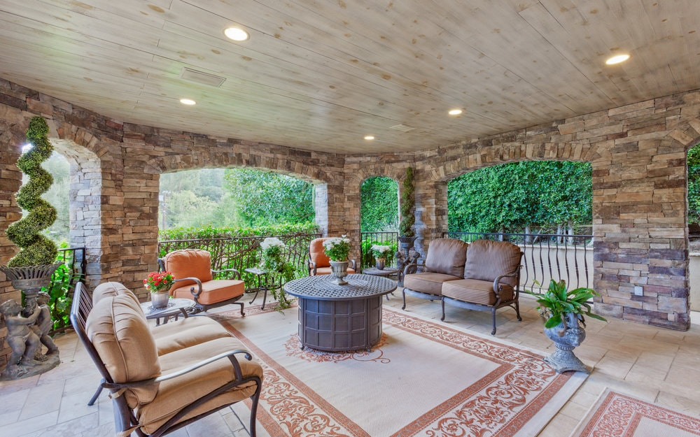 This is a charming covered patio with wide open arches and textured stone pillars surrounding the wrought-iron arm chairs adorned with potted plants. Images courtesy of Toptenrealestatedeals.com.