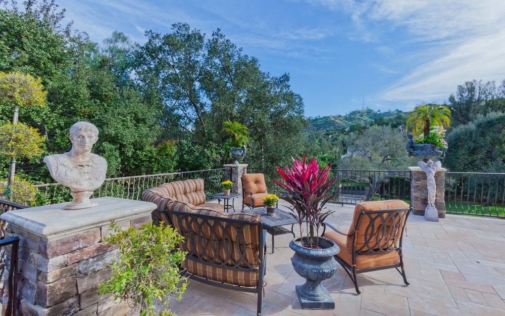 This is the outdoor patio with a cushioned wrought-iron sofa set facing a beautiful scenic view of treetops. Images courtesy of Toptenrealestatedeals.com.