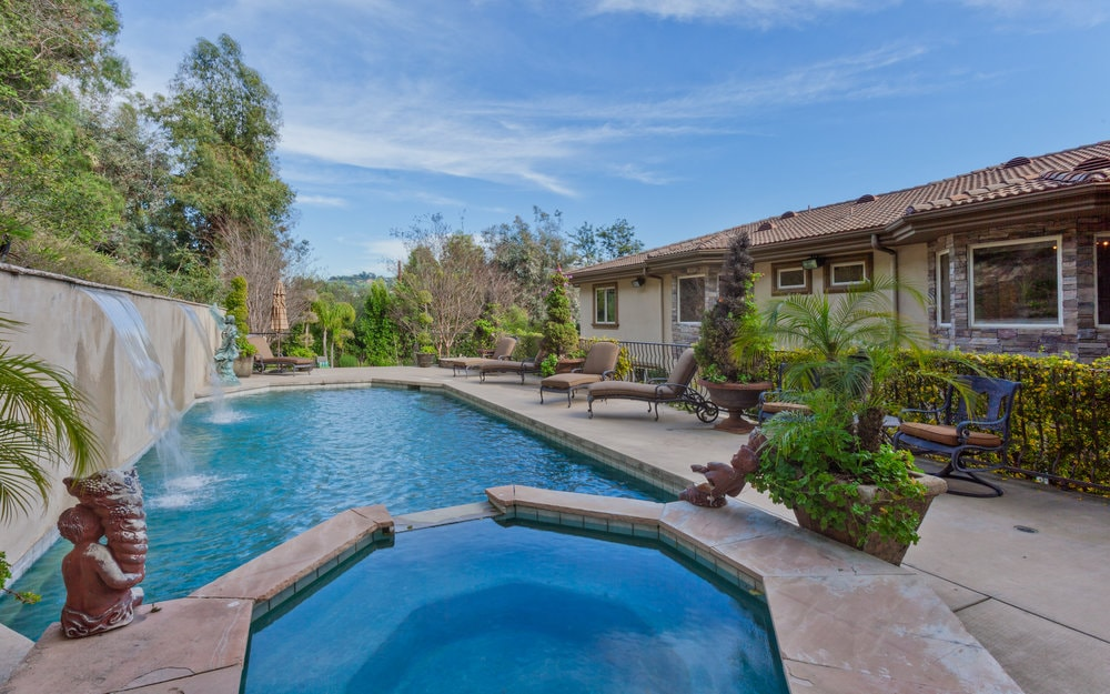 This is a close look at the beautiful pool of the house with an attached jacuzzi-type pool on the side. The pool-side area is adorned with potted plants and various lawn chairs. Images courtesy of Toptenrealestatedeals.com.