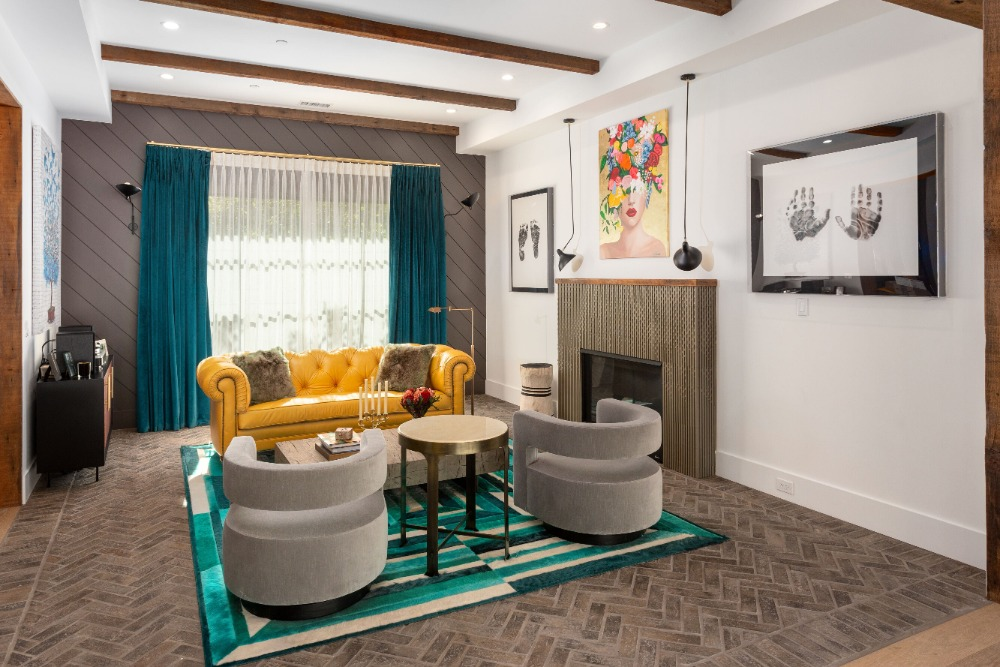 A living space featuring a set of attractive seats on top of a stylish area rug. There's a fireplace on the side. Images courtesy of Toptenrealestatedeals.com.