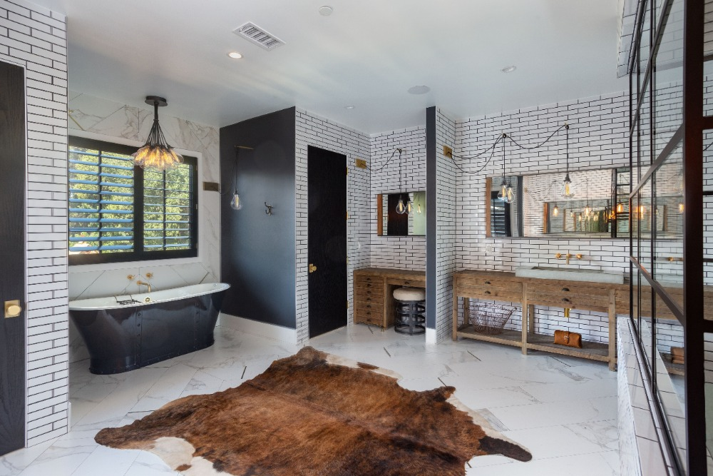 Primary bathroom offering a classy freestanding tub by the window, a rustic sink counter and a walk-in shower and toilet area. Images courtesy of Toptenrealestatedeals.com.