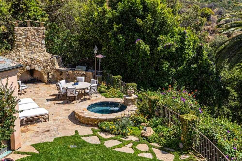 This is a top view of the lovely patio that has an outdoor dining area and a fountain on its concrete floor that transitions beautifully to the grass lawn with a walkway.