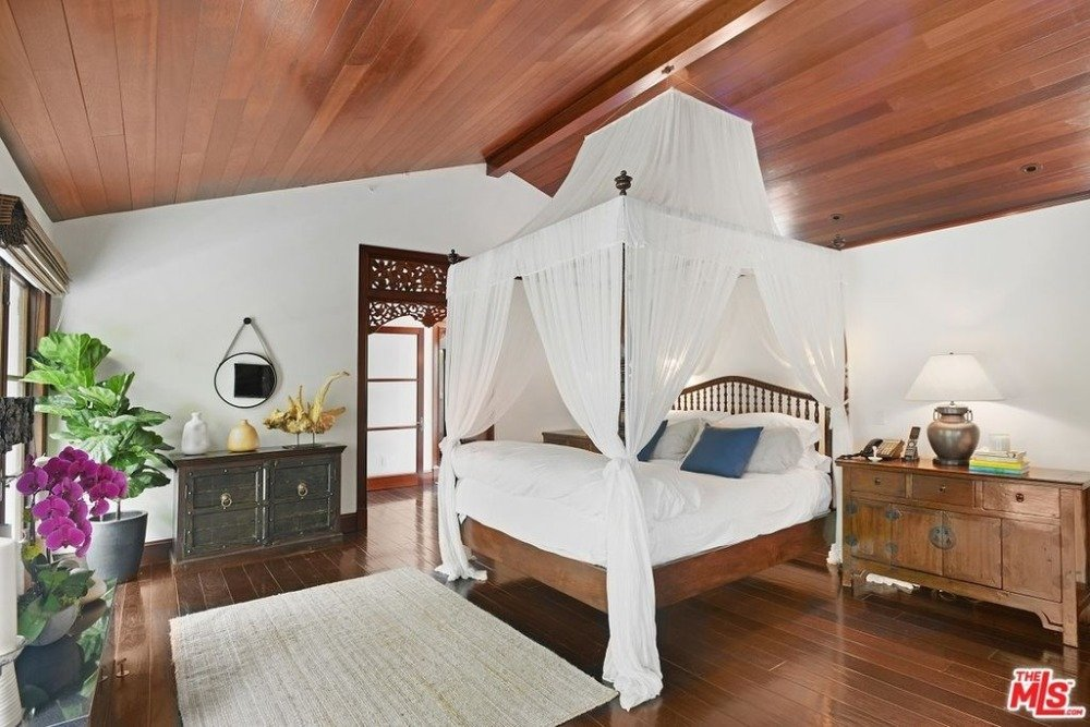Primary bedroom with a lovely bed set. The room has hardwood flooring and a wooden ceiling. Images courtesy of Toptenrealestatedeals.com.