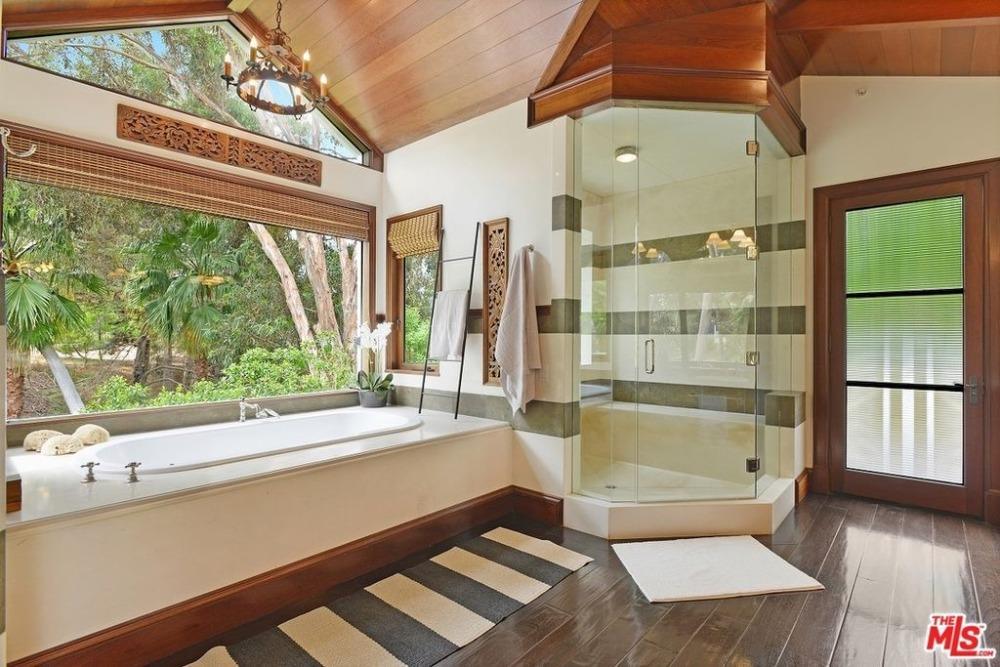 Primary bathroom featuring a drop-in soaking tub by the window and a walk-in shower room. Images courtesy of Toptenrealestatedeals.com.