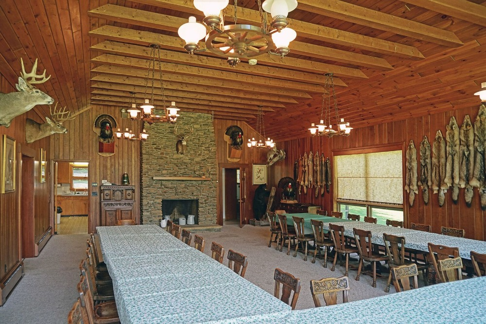 The lodge also boasts a massive dining hall with three large dining table sets with a stone fireplace. Images courtesy of Toptenrealestatedeals.com.