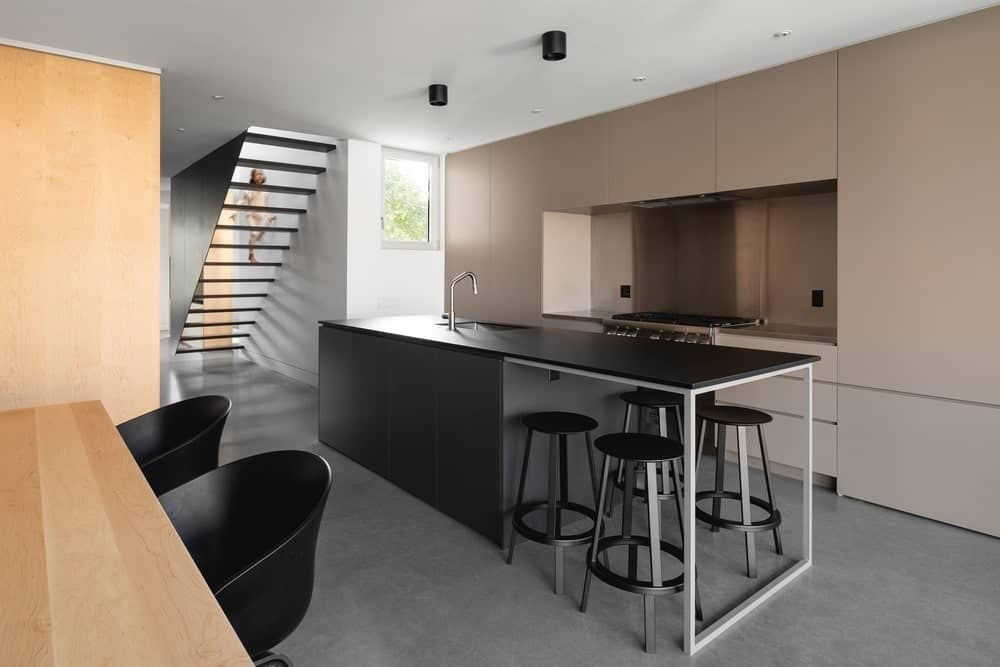 This is a modern kitchen with a long black kitchen island that gives it a long and narrow design. The edge of the island extends to a modern built-in table paired with black stools.