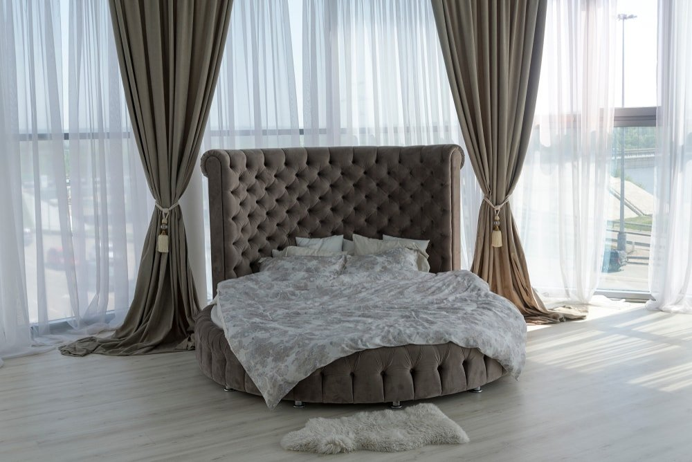Luxury bedroom with a round bed and full-length draperies and windows.