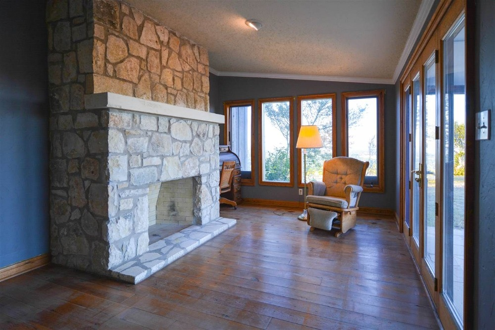 Here's an empty living space featuring hardwood flooring and a large stone fireplace. Images courtesy of Toptenrealestatedeals.com.