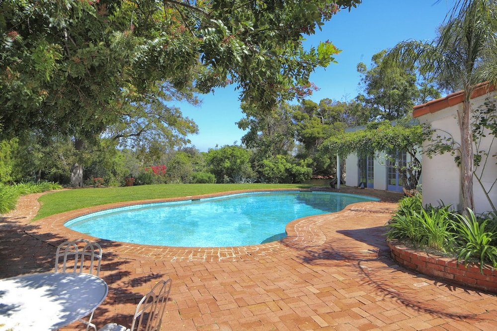 The backyard pool has a lovely kidney shape to it surrounded by earthy beige tiles that transitions to a grass lawn bordered with trees and shrubs. Images courtesy of Toptenrealestatedeals.com.