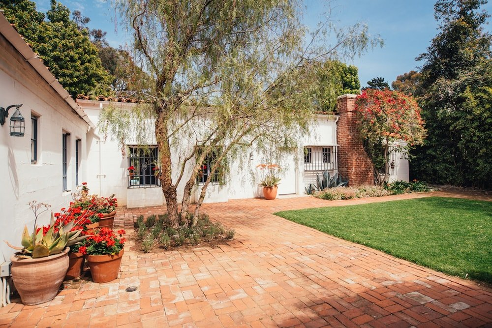 This is a closer look at the main entrance of the house that has earthy terracotta brick walkways bordering the green grass lawn. This area is adorned with various potted flowering plants and a tree. Images courtesy of Toptenrealestatedeals.com.