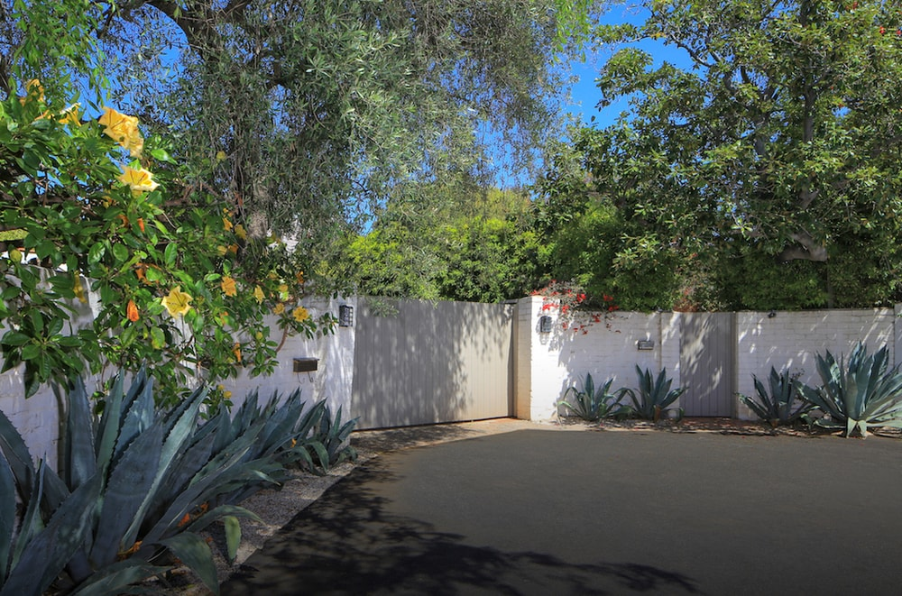 This is the main gate of the property supported by tall white concrete walls and augmented by tall trees and shrubs for additional privacy. Images courtesy of Toptenrealestatedeals.com.