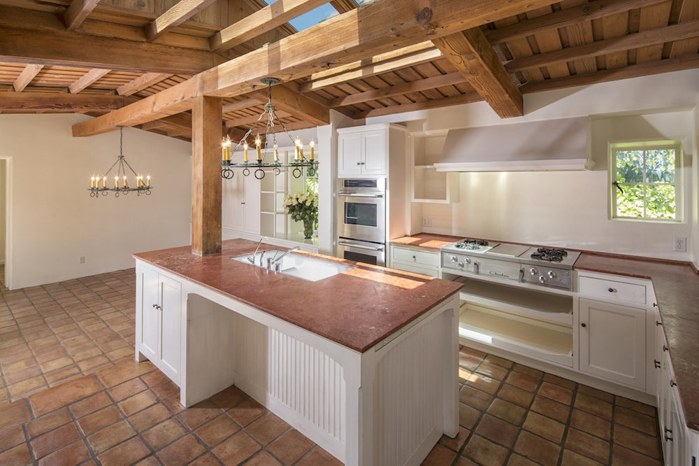 This is the charming kitchen that has a wooden cathedral ceiling with exposed beams. These pair well with the terracotta flooring tiles that contrast the bright white walls and built-in cabinetry that houses the appliances. Images courtesy of Toptenrealestatedeals.com.