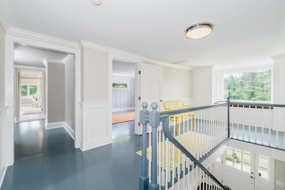 This is the second floor landing of the house with gray flooring to match the gray banisters contrasted by the bright walls and ceiling. Images courtesy of Toptenrealestatedeals.com.