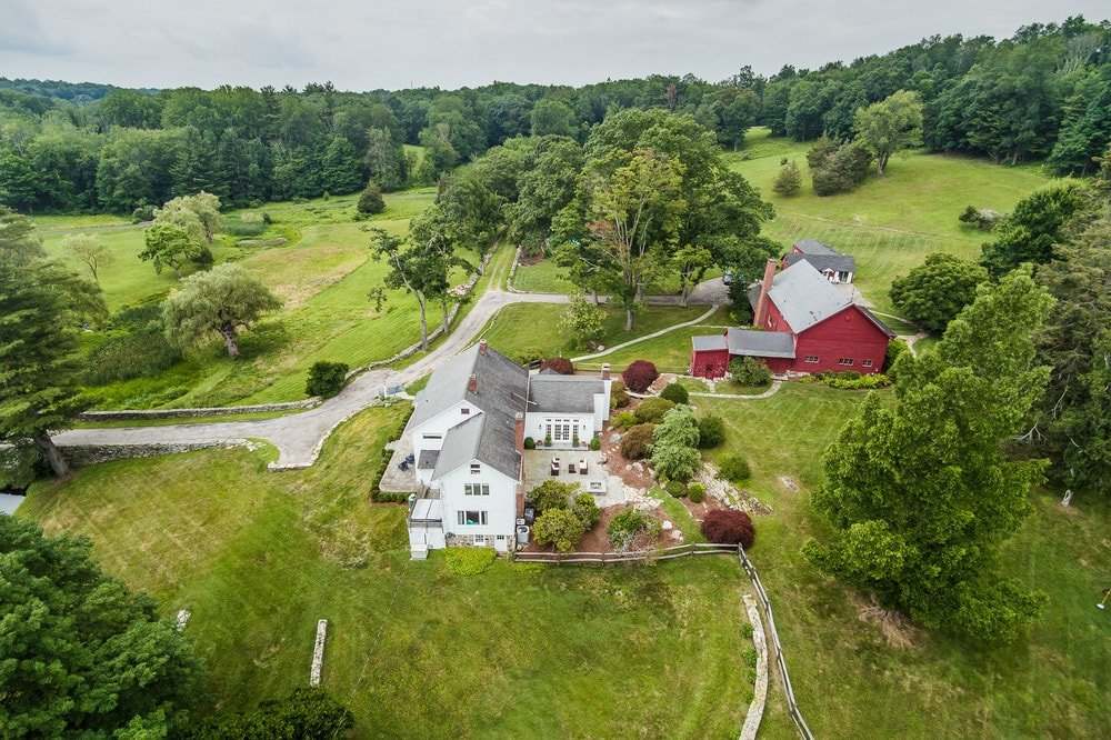 This is the aerial view of the property showing its two large structures and the surrounding lush fields of grass and tall trees. Images courtesy of Toptenrealestatedeals.com.