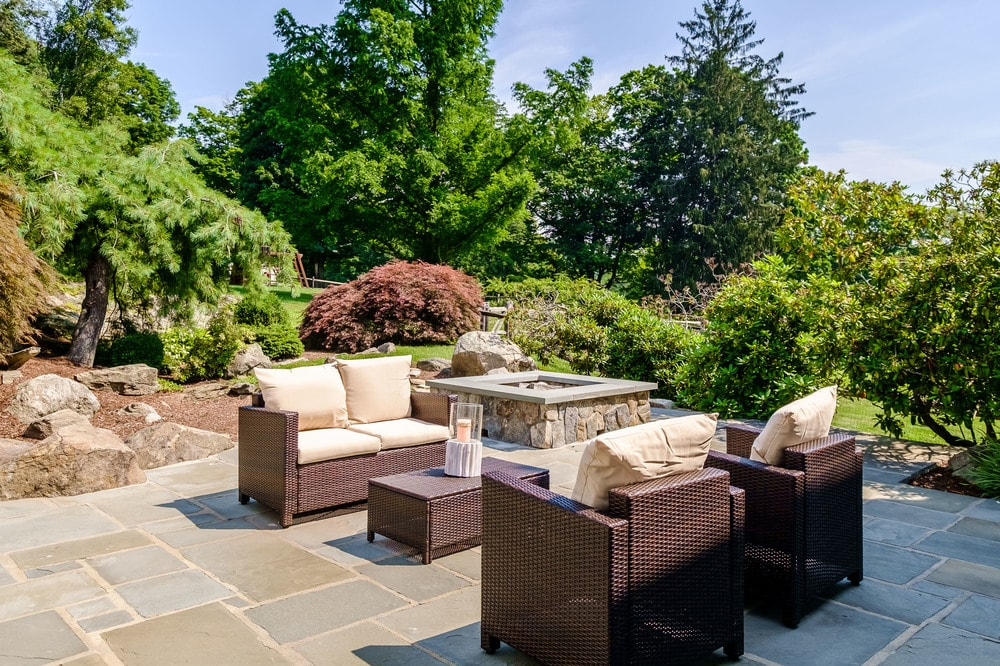 This is a closer look at the lovely sitting area of the back of the house with dark brown woven wicker sofa set and a background of lush landscaping. Images courtesy of Toptenrealestatedeals.com.