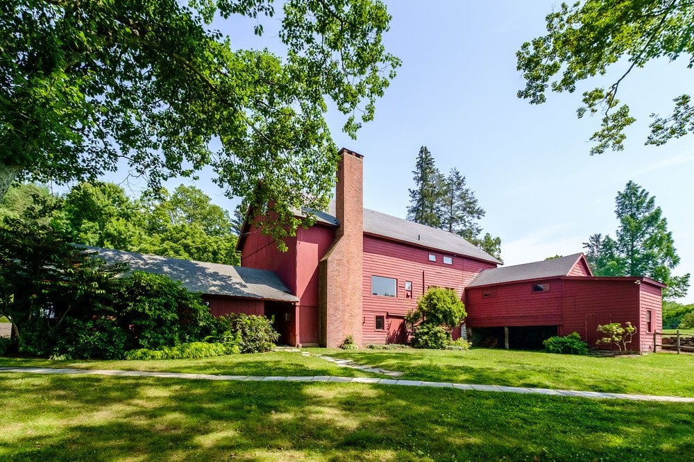 This other view of the barn exterior shows the tall chimney towering on the side with the same reddish tone as the exteriors of the barn. Images courtesy of Toptenrealestatedeals.com.