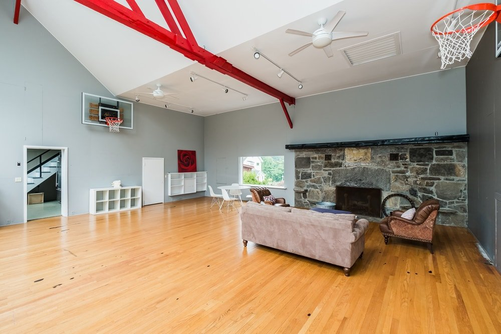 This is the indoor basketball court of the property fitted with a lovely living room at the corner that has a large stone fireplace across from the gray sofa set. Images courtesy of Toptenrealestatedeals.com.
