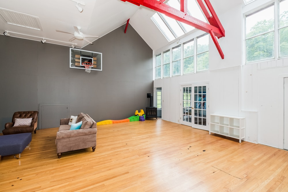 This other view of the indoor basketball court shows the massive size of the area with a tall arched white ceiling augmented by the skylights that bring in natural lighting. Images courtesy of Toptenrealestatedeals.com.