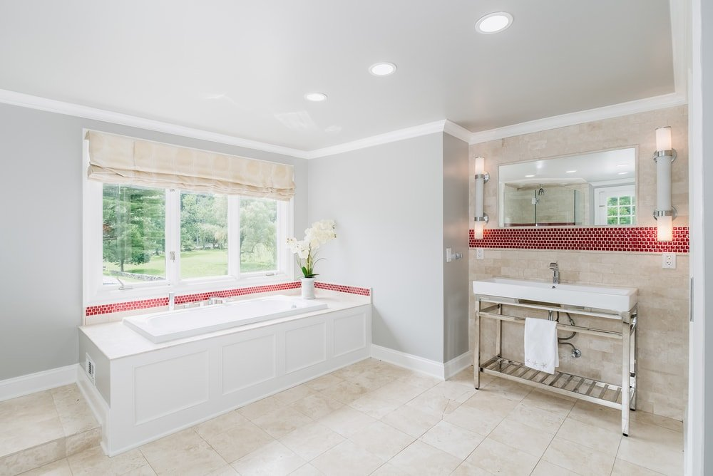 This is a bright and white primary bathroom complemented by the light beige flooring tiles and the red line that accents the walls running above the bathtub at the window and the sink area beside it. Images courtesy of Toptenrealestatedeals.com.