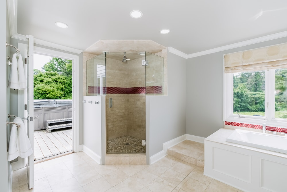 This other view of the primary bathroom features the glass-enclosed walk-in shower area just beside the bathtub and the door. Images courtesy of Toptenrealestatedeals.com.