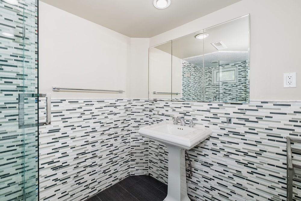 This bathroom has patterned tiles on the lower half of its walls to serve as backsplash and complement the pedestal sink across from the shower area. Images courtesy of Toptenrealestatedeals.com.