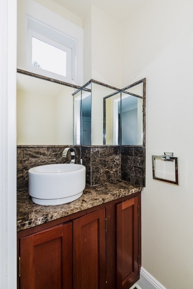 This bathroom has a lovely dark marble countertop to its vanity extending to the backsplash that makes the white freestanding sink stand out. Images courtesy of Toptenrealestatedeals.com.
