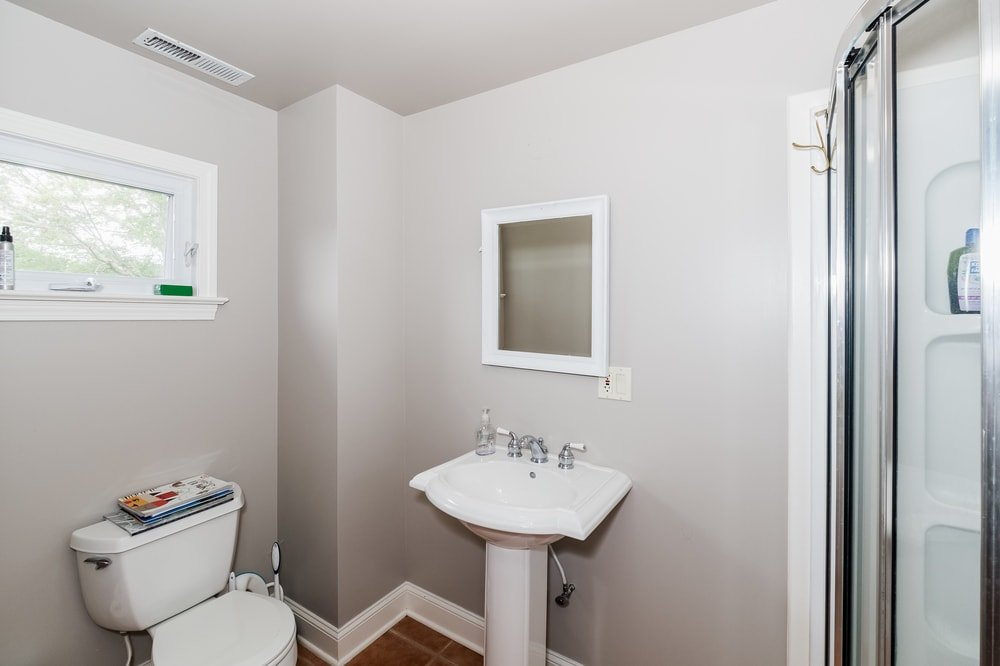 This is a simple bathroom with gray walls to complement the white porcelain pedestal sink and toilet. Images courtesy of Toptenrealestatedeals.com.