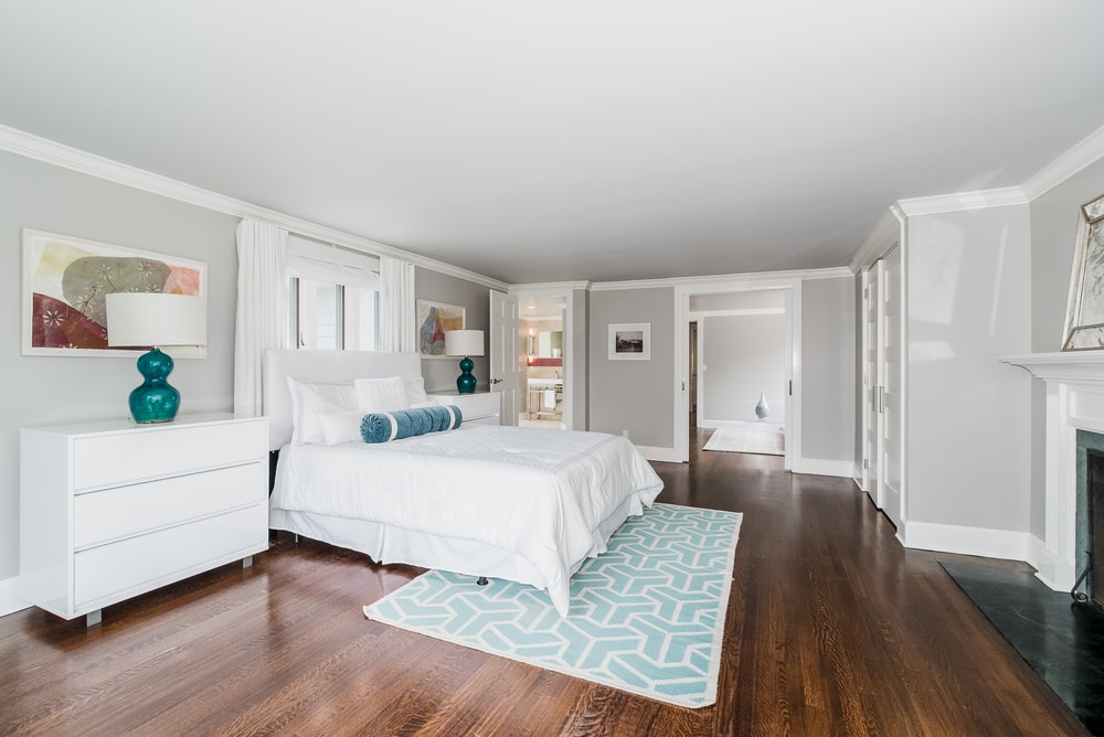 This other view of the primary bedroom shows that the large white bed is flanked by matching white bedside drawers bearing blue-gray decorative lamps to stand out against the light gray walls. Images courtesy of Toptenrealestatedeals.com.