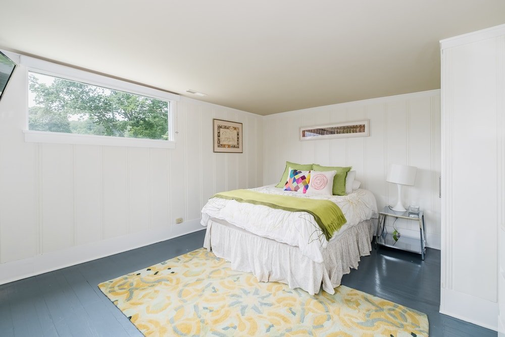 This is a homey bedroom with a splash of color coming from the sheets and pillows of the bed that blends well with the surrounding light beige walls and ceiling. Images courtesy of Toptenrealestatedeals.com.