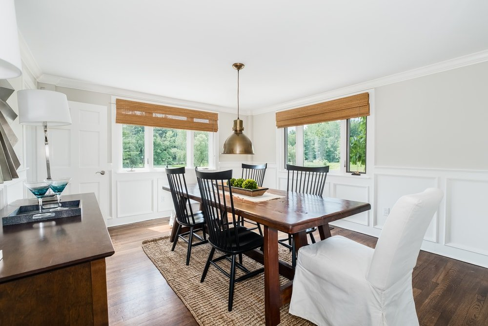 This is the dining room with a rectangular wooden dining table surrounded by black slat-back chairs to contrast the surrounding bright walls and wainscoting. Images courtesy of Toptenrealestatedeals.com.