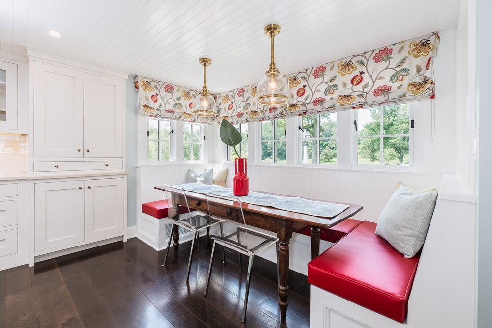 This is a closer look at the informal dining area at the edge of the kitchen. It has a U-shaped built-in booth-style bench with red cushions paired with a small wooden dining table that matches the hardwood flooring. Images courtesy of Toptenrealestatedeals.com.
