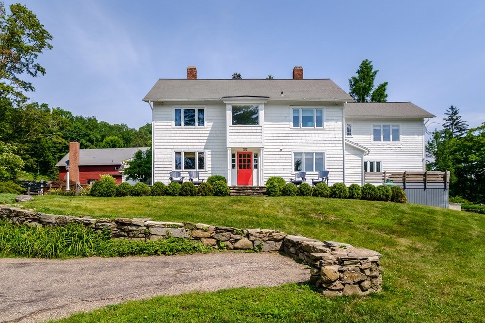 This is a gorgeous farmhouse with bright white exterior walls to make the red door stand out adorned by the surrounding landscape of lush green grass, shrubs and trees. Images courtesy of Toptenrealestatedeals.com.