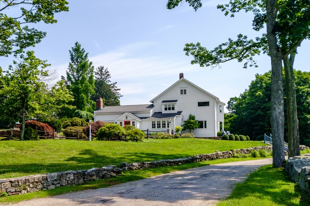 This view of the house shows the driveway leading to the bright white home that if framed by the tall trees and the lush grass lawns. Images courtesy of Toptenrealestatedeals.com.