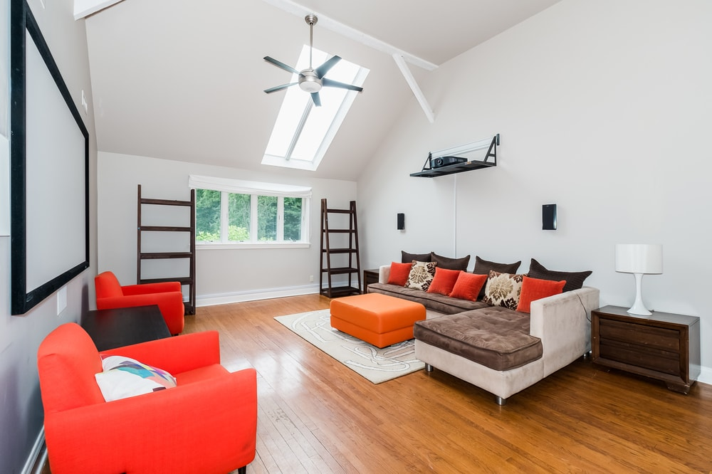 This other living room has bright armchairs, pillows and ottoman to stand out against the bright walls and arched ceiling with a skylight. Images courtesy of Toptenrealestatedeals.com.
