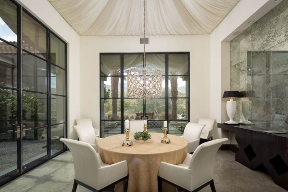 This is an intimate dining room with a small round dining table surrounded by white upholstered chairs with black legs. These pair well with the frames of the large glass walls and the various room accents scattered all around.