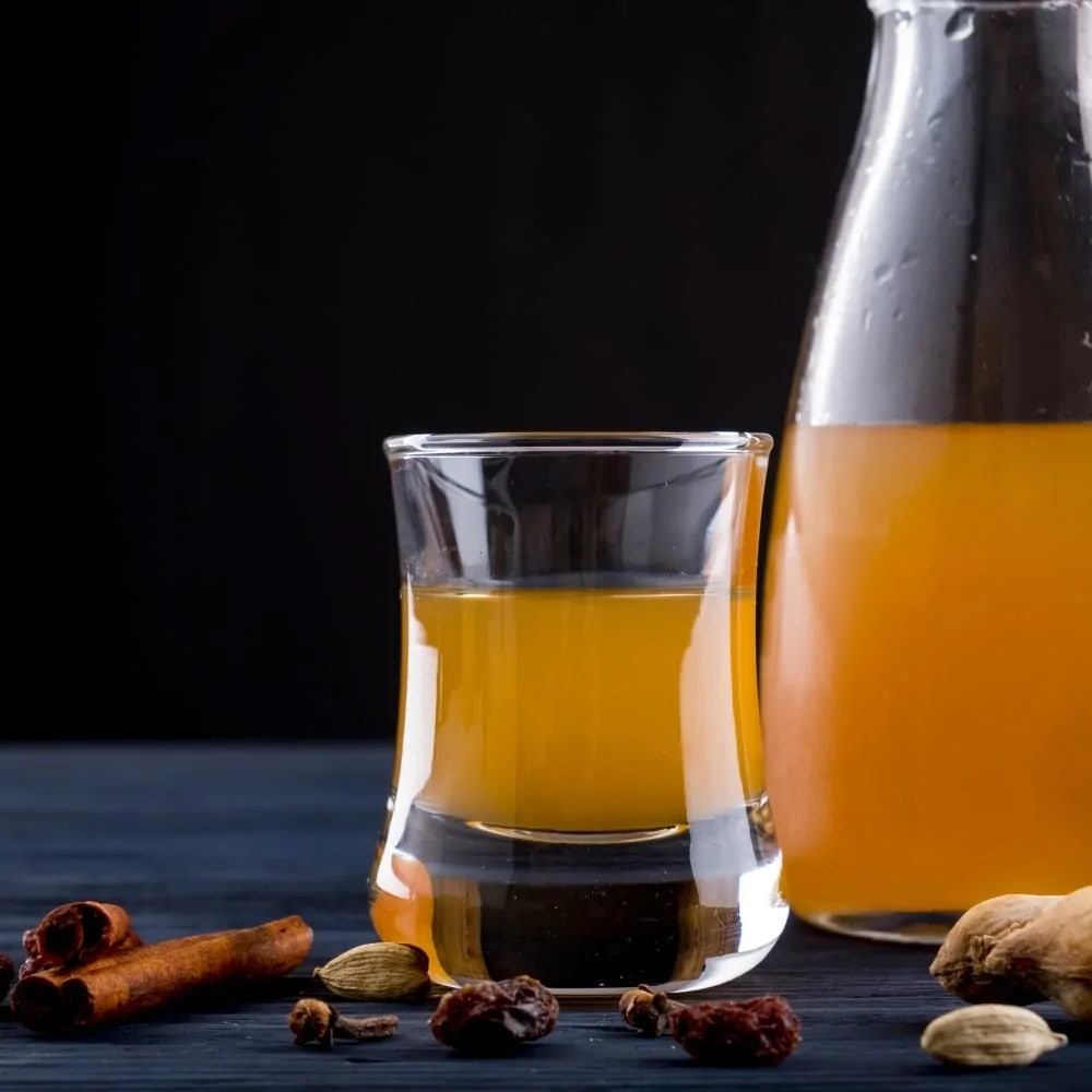 A glass and a pitcher of mead surrounded by cinamon, raisins, and nuts on a dark background.