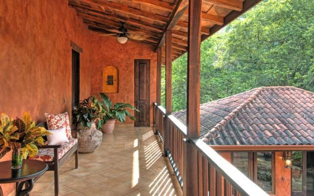 This is the balcony looking over the front courtyard. It has charming wooden railings that match with the arched wooden ceiling filled with exposed beams. These are then complemented by the potted plants and earthy exterior walls. Images courtesy of Toptenrealestatedeals.com.